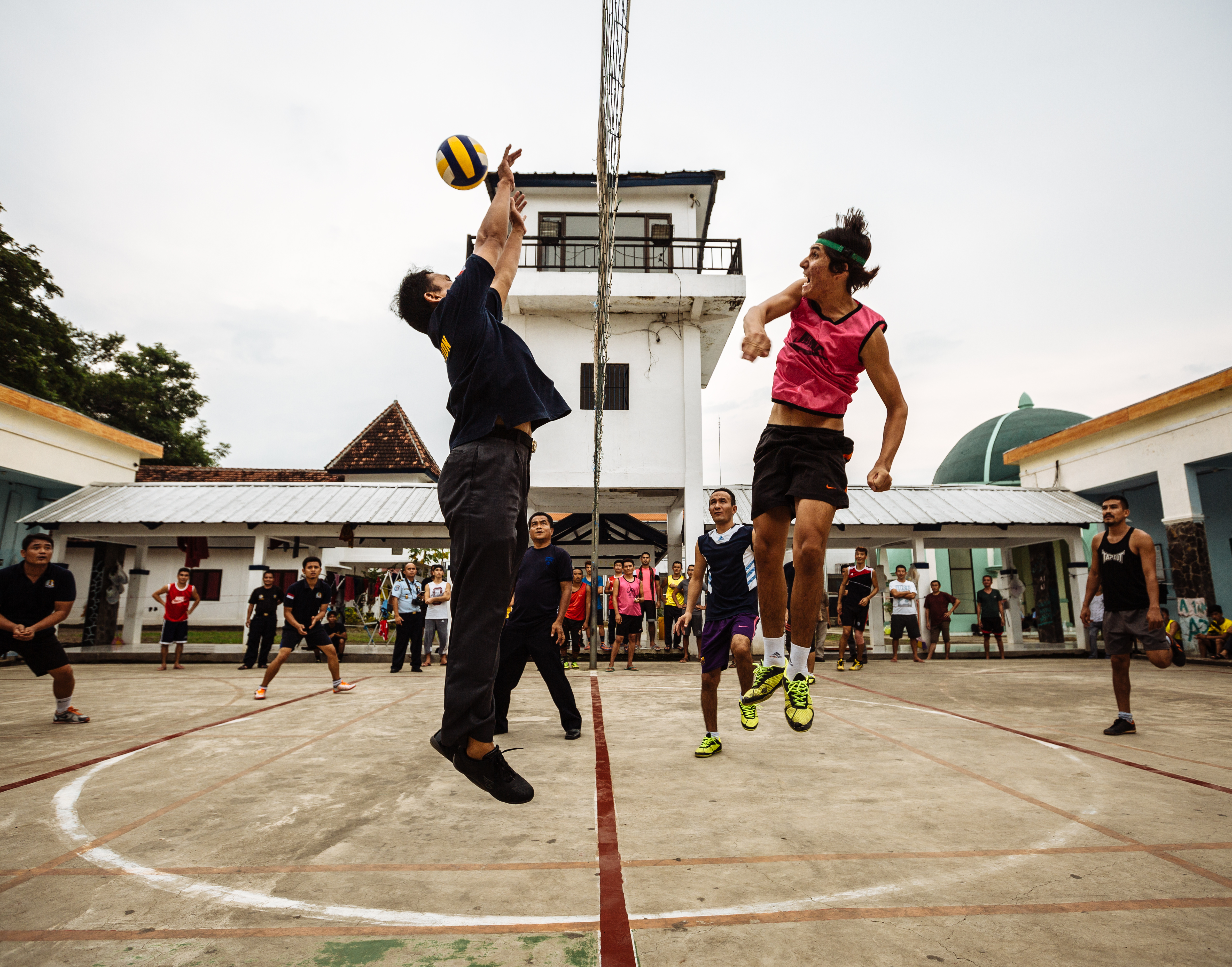 Afghan refugees face off against Indonesian immigration officers in a friendly volleyball match in Java, Indonesia. Many of the asylum seekers have been waiting for years to be processed and approved for resettlement. Until the day comes for them to be resettled, they try to keep their spirits up through various recreational activities.