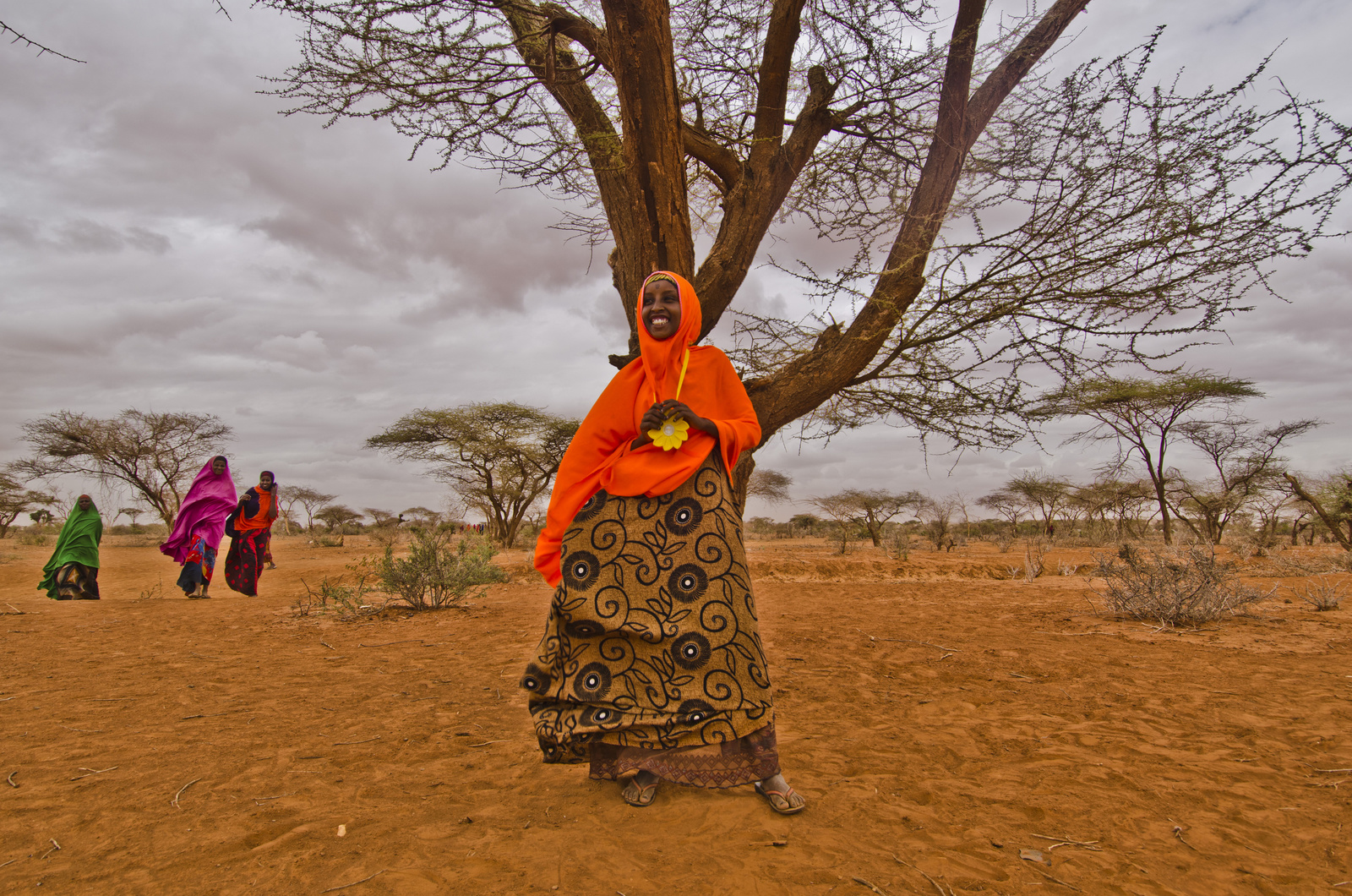Displaced Somali beneficiary wears Little Sun around her neck and looks smilingly into the horizon.