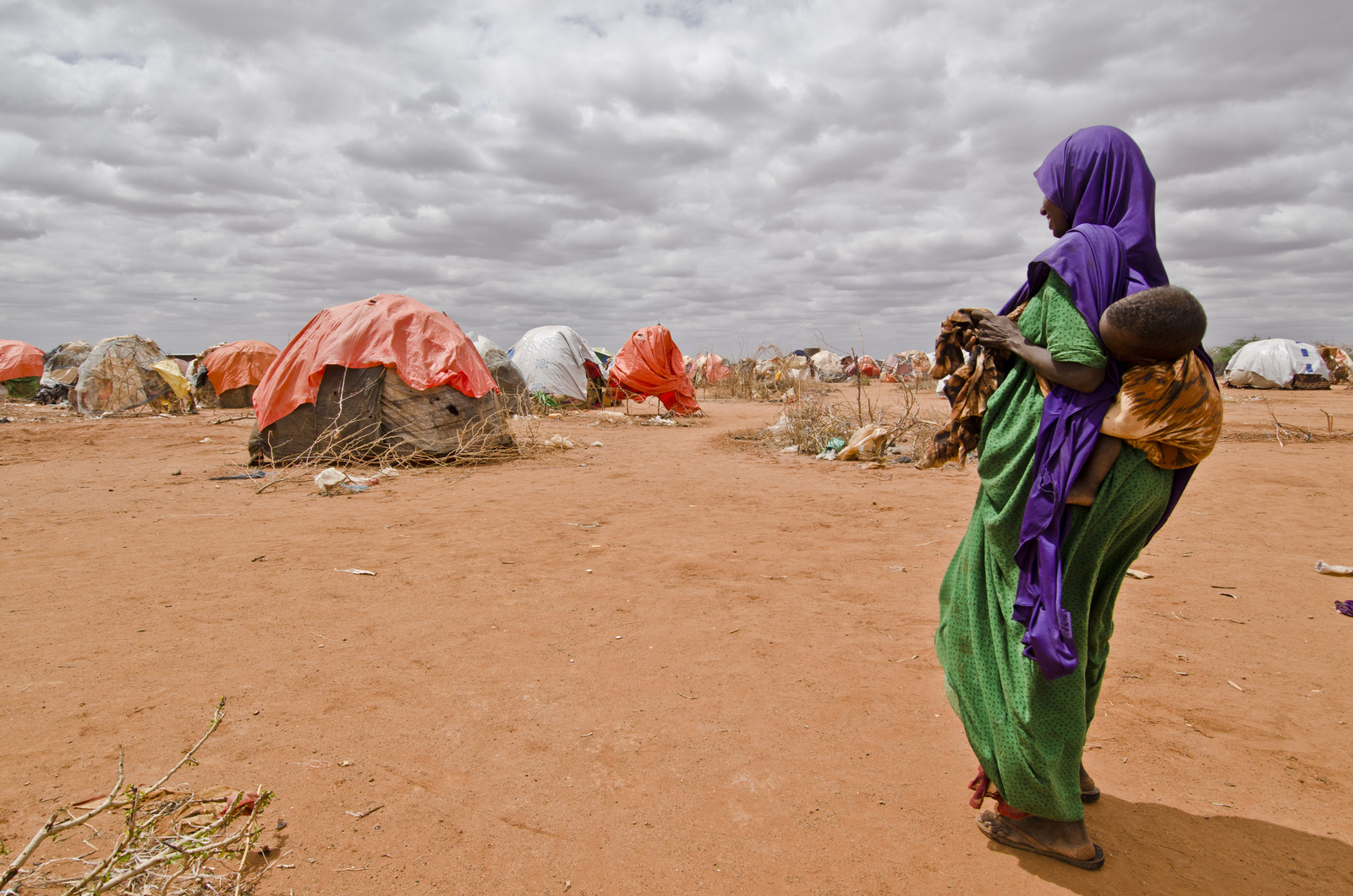Displaced Somali woman with her baby on her back looking into the horizon strewn with make-shift shelters.