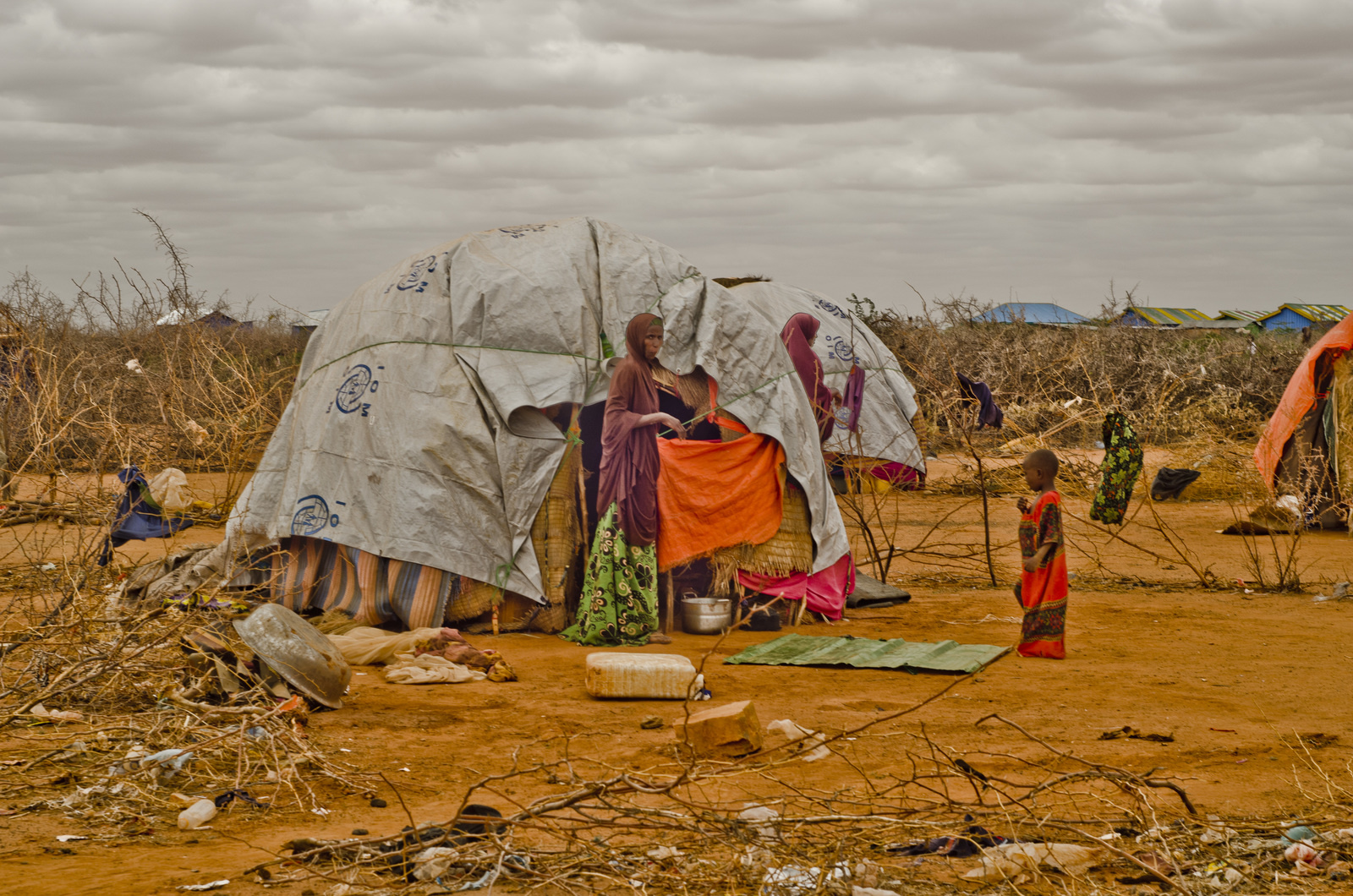Mother beckoning her child to enter their shelter made of wood and plastic sheeting in Airstrip Area Displacement Site, Dolo Ado, Somali Region