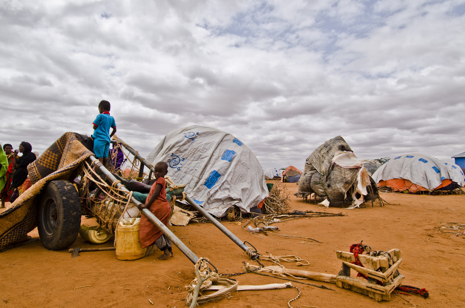 Displaced children play with a cart, one looks into the horizon with an overview of the displacement site while the other looks at the camera.
