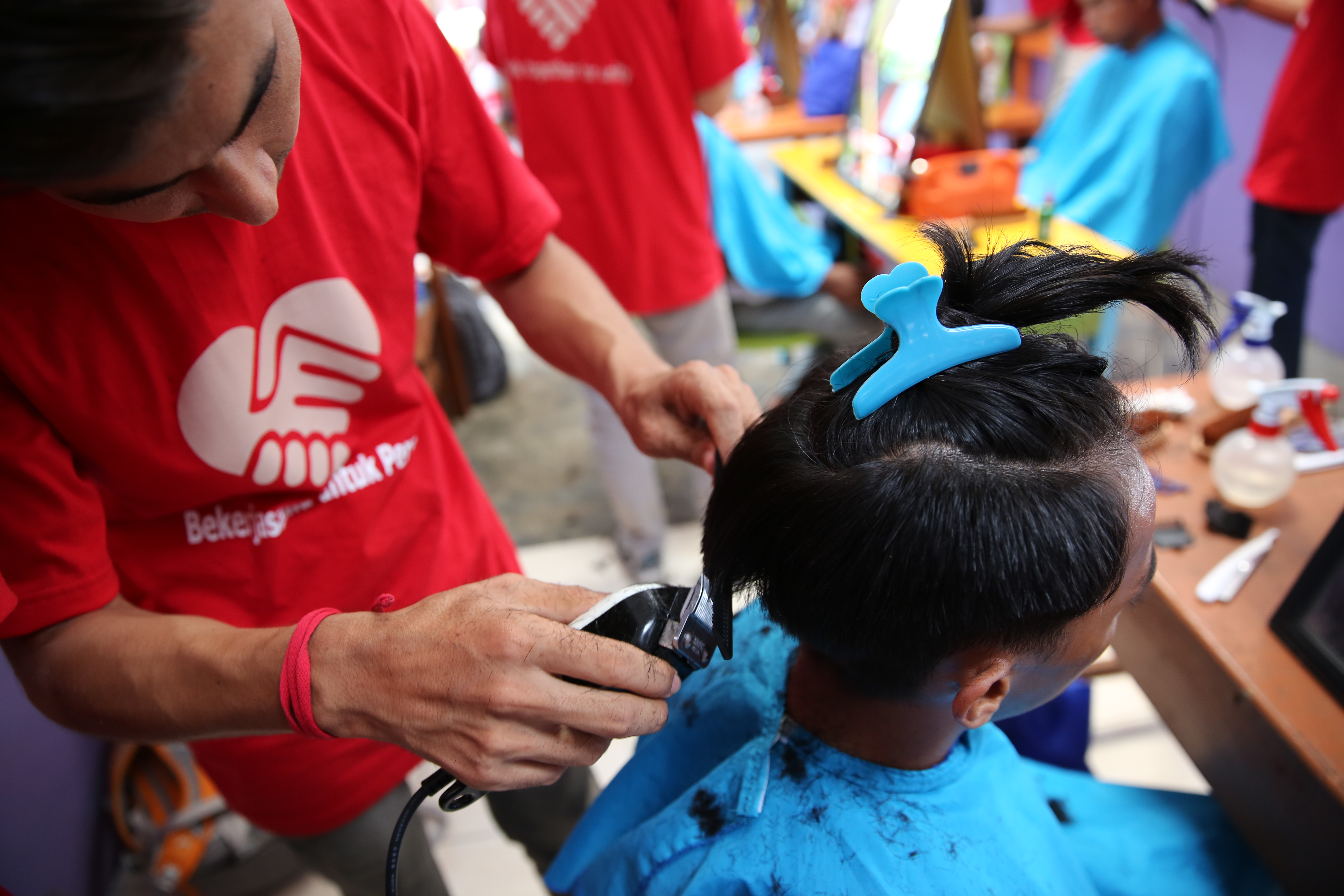 """Refugees from five nations living in Medan, Indonesia with IOM's assistance provided 20 street children and dozens of local residents a special """"spa day"""" treatment prior to the Idul Adha holiday weekend. Fourteen young Afghan, Iraqi, Iranian, Palestinian and Sudanese men who graduated from a three-month hair stylist vocational training program organized by IOM have been volunteering their talents at orphanages and other facilities since mid-2017."""