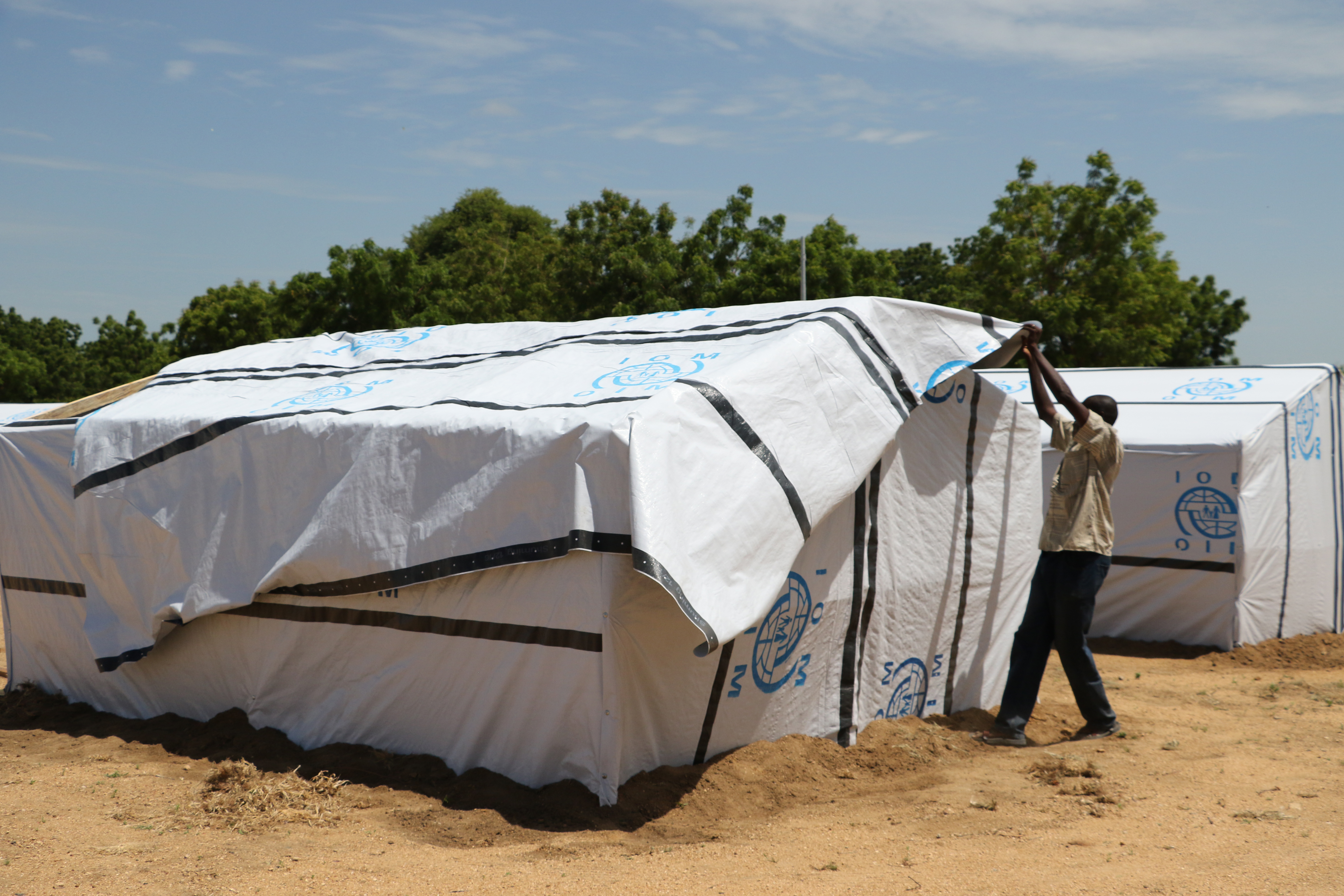 IOM Director General William Lacy Swing spent three days meeting with some of the internally displaced at camps and in communities in the hardest hit areas of Borno state, the epicentre of the conflict. IOM's emergency response is based in Maiduguri, the capital of Borno and the birthplace of Boko Haram.  Shelter under construction in Gwoza camp in Borno State.  Photo: Julia Burpee / UN Migration Agency (IOM) 2017