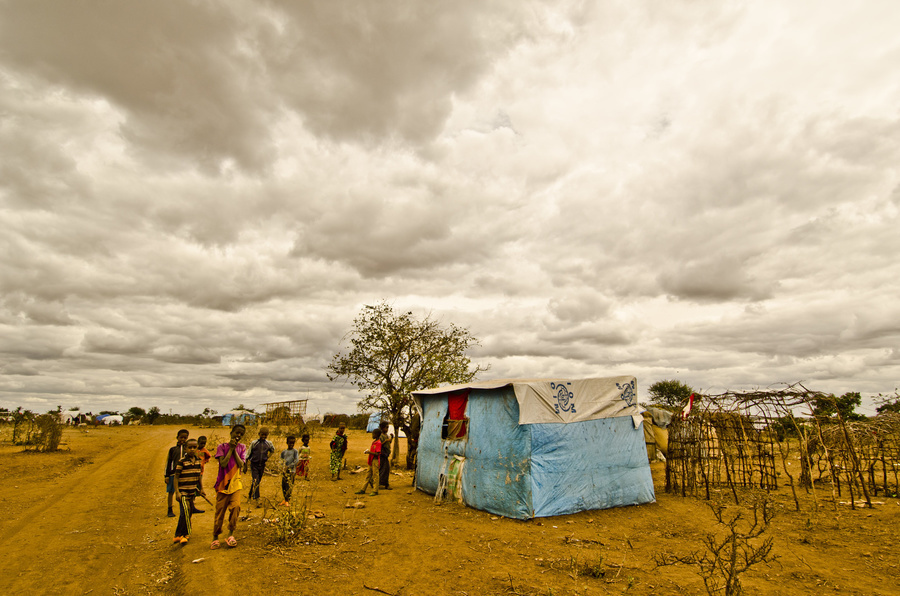 Displaced children curiously walk towards camera and pass by two make-shift shelters: one fully finished make-shift shelter made of plastic sheeting, and another at first stage of construction with frame made of wooden poles. Photo: Rikka Tupaz / UN Migration Agency (IOM) 2017