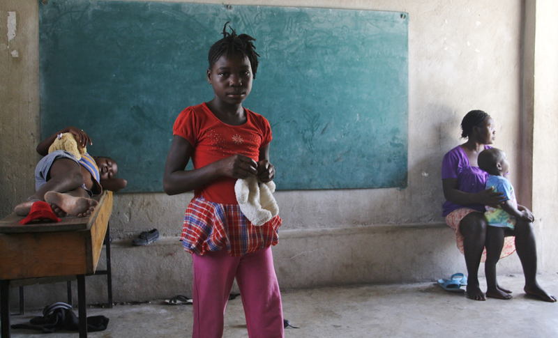 A girl stands in one of the classrooms currently used as dormitories by families having recently crossed into Haiti from the Dominican Republic. © IOM/Ilaria Lanzoni 2015