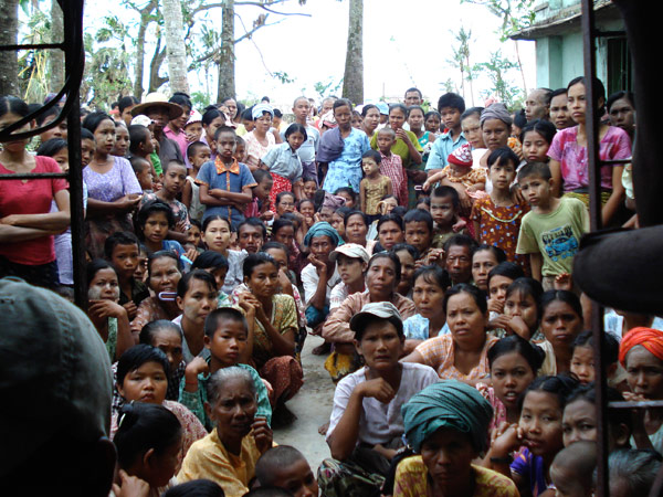 WAITING TO BE TREATED. Cyclone survivors in a village in the Delta patiently wait for IOM staff to begin the medical check-ups. As of 29 July 2008, mobile medical teams have treated more than 24,600 patients in 327 villages in the Delta townships of Bogale, Pyapon and Mawlamyinegyun. © IOM 2008 - MMM0205