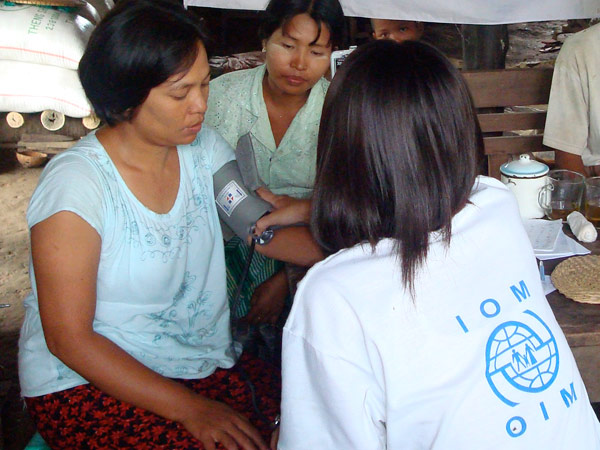 EXAMINING CYCLONE SURVIVORS. An IOM medical staff checks the blood pressure of a patient in a village in the Delta. As of 29 July 2008, mobile medical teams have treated more than 24,600 patients in 327 villages in the Delta townships of Bogale, Pyapon and Mawlamyinegyun. © IOM 2008 - MMM0158