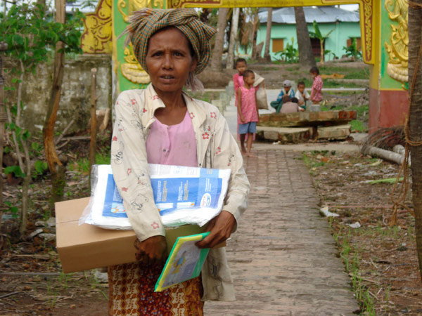 MUCH WELCOME ASSISTANCE. A cyclone survivor carries a relief kit distributed by IOM. Included in the kit are chlorine for water purification, hygiene/family kits, rain ponchos and insecticide-treated mosquito nets. © IOM 2008 - MMM0208