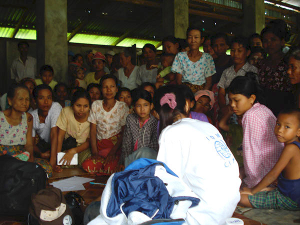 ALL EYES AND EARS. An IOM medical staff interviews a patient as other cyclone survivors observe curiously. As of 29 July 2008, mobile medical teams have treated more than 24,600 patients in 327 villages in the Delta townships of Bogale, Pyapon and Mawlamyinegyun. © IOM 2008 - MMM0214