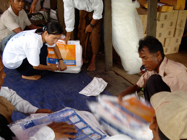 PREPARING FOR DISTRIBUTION. Mobile staff prepare insecticide-treated mosquito nets as part of the relief kits being distributed by IOM. Other relief items include tarpaulins, jerry cans, chlorine for water purification, hygiene/family kits, and rain ponchos. © IOM 2008 - MMM0174