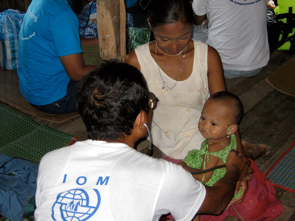 A WORRIED MOTHER. A mother watches as an IOM medical staff checks the heart beat of her baby. Cyclone survivors often suffer from the effects of unclean water and food, lack of proper shelter and clothing, and a lack of proper sanitation. © IOM 2008 - MMM0116