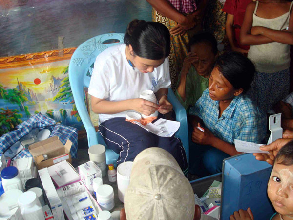 PREPARING THE RIGHT DOSAGE. A member of an IOM mobile medical team prepares medicine for a patient. As of 29 July 2008, mobile medical teams have treated more than 24,600 patients in 327 villages in the Delta townships of Bogale, Pyapon and Mawlamyinegyun. © IOM 2008 - MMM0080