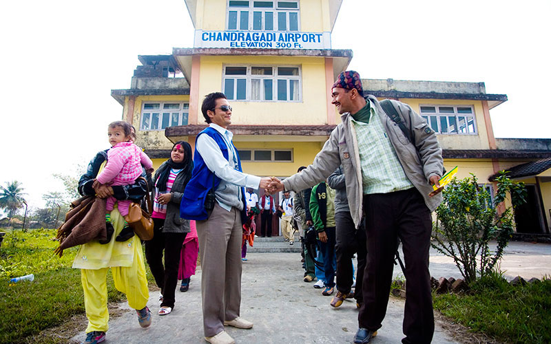 A Bhutanese refugee thanks and bids farewell to an IOM staff who assisted them at the airport. The refugees boarded a plane that took them to Kathmandu. IOM's resettlement activities for refugees include medical screening, cultural orientation and travel arrangements of refugees accepted for resettlement. © IOM/Kari Collins 2009 - MNP0071