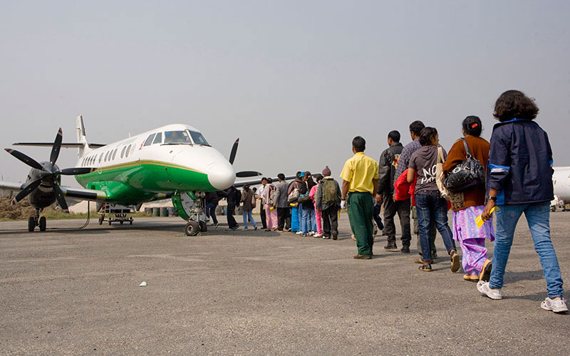 Bhutanese refugees board the plane for a domestic flight to Kathmandu. IOM's resettlement activities for refugees include the processing of cases referred to resettlement countries by the UNHCR, medical screening, cultural orientation and travel arrangements of refugees accepted for resettlement. © IOM/Kari Collins 2009 - MNP0069