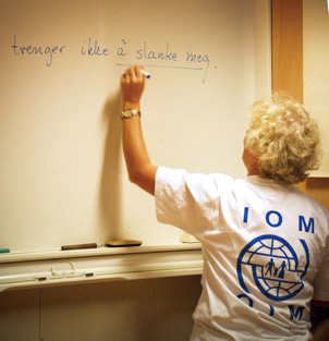 An IOM staff goes to the board to stress a point during a language training class with Polish construction workers as participants. © IOM 2008