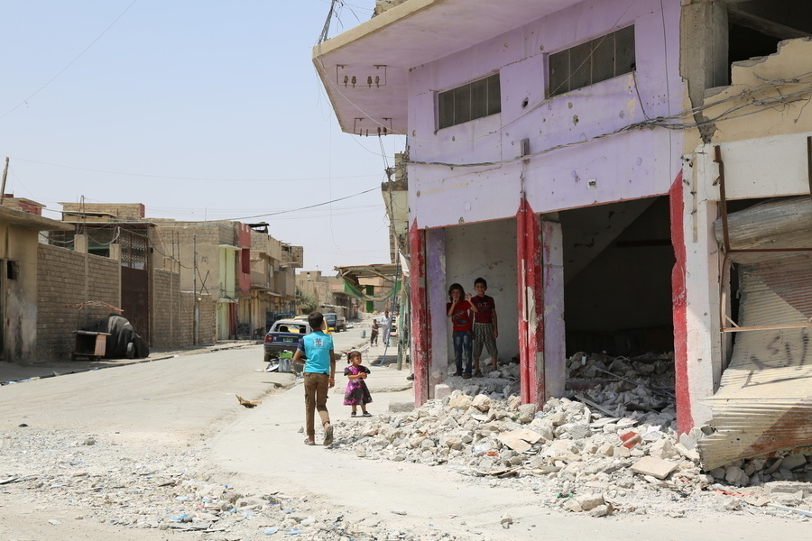 This neighborhood was relatively less damaged and sporadic movement of people could be seen. these children played in the rubble of this damaged sop.