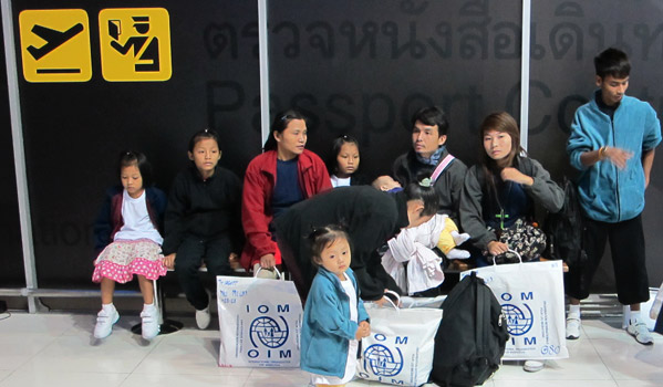 Labur Paw (3, centre) in front of her mother Ma Lay Lay, the 100,000th refugee assisted to resettle by IOM Thailand at Bangkok International Airport prior to their early morning flight to the USA. © IOM 2012