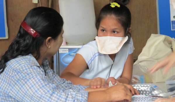 IOM translator DeeDee, with a TB patient at an IOM health post in Mae Lat Camp. © IOM 2012