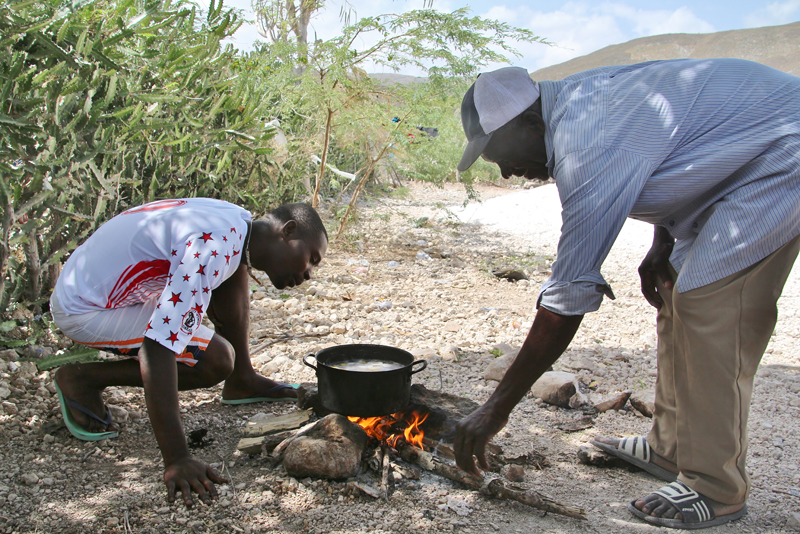 Fefé, 29, and his father, André Joseph, 53, are preparing a meal for their family, which also includes Fefé's mother and his two children, aged 6 and 4. André Joseph has spent most of his life in the Dominican Republic, where he arrived when he was 12. He was as an agricultural worker. Fefé joined him from Haiti three years ago to work in a sugarcane plantation. None of them hold identification documents in either country. © IOM/Ilaria Lanzoni 2015