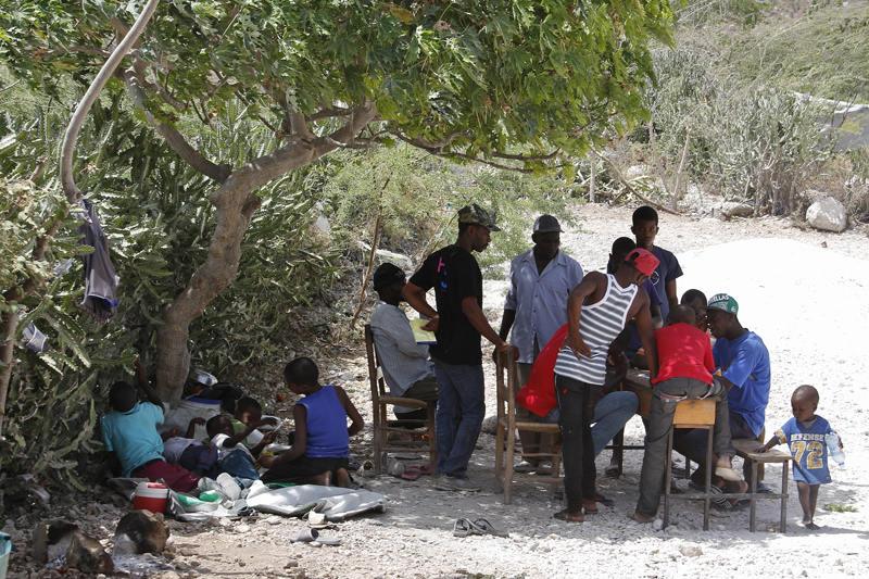 With little to do, men gather under a tree playing domino to kill time. Children play and sit in the shade. The heat is scorching and there is dust everywhere. © IOM/Ilaria Lanzoni 2015