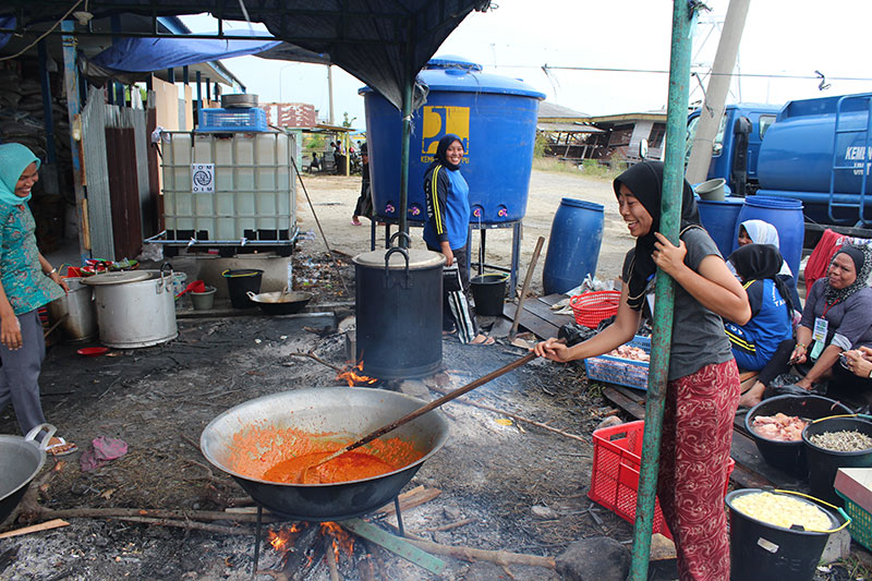 Local volunteers cook IOM-sourced food for migrants from Bangladesh and Myanmar at Langsa camp.  © IOM/Joe Lowry 2015