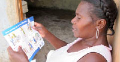 A camp resident reads a cholera information kit distributed by IOM as part of a range of activities aimed at preventing the further spread of the disease. Aside from large-scale hygiene promotion, IOM also plans to establish first-line monitoring for cholera and rapid treatment and referral, map Cholera Treatment Units (CTUs) and enhance latrine sanitization efforts, and water testing and treatment. © IOM 2010