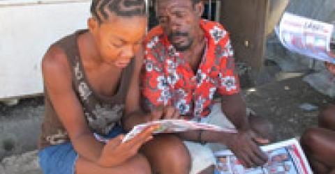 Camp residents read an issue of Chimen Lakay, IOM Haiti's graphic cartoon newspaper. A special issue of the newspaper has been released on the subject of cholera prevention. The name Chimen Lakay means