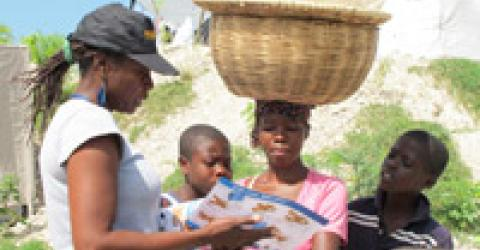 An IOM staff distributes information materials about cholera prevention. The Organization also distributed urgently needed medical supplies to health facilities as part of its multi-pronged response to fight the cholera epidemic in Haiti. © IOM 2010