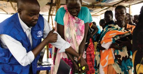 An IOM staff assists internally displaced persons (IDPs) at the UN House's protection of civilian (PoC) site in Juba. The Organization was able to complete the registration of a total of 28,968 IDPs using a biometric registration process. © IOM 2014