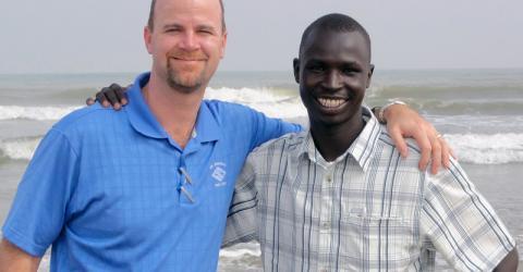 Nhial (a la derecha) con su padre de acogida, Dan Pickering. Cuando Nhial Malia tenía 11 años de edad, fue trasladado por la OIM desde un campamento de refugiados en la región occidental de Etiopía hasta Houston, Texas.