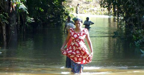 Ms. Aarachchika Nilankani Pushpakumari struggles through high floodwater to reach an IOM distribution in south of Colombo at the weekend. © IOM 2014