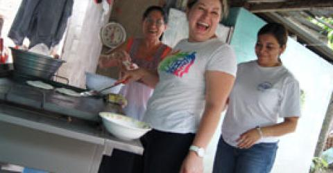 Cesia works alongside her mother in their food business. IOM's Cecilia Ramirez provides reintegration support.