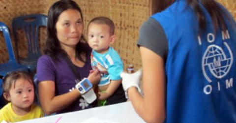 Twenty-four-year-old Ma Lay Lay and her three-year-old Labur Paw and eleven-months-old Ywar Mar Ser are screened by an IOM nurse at Mae La camp. She is the 100,000th refugee that IOM has helped to leave Thailand since 2004 when large-scale resettlement operations resumed. © IOM 2012
