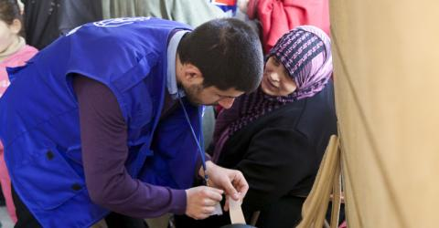 IOM Operations staff placing tags on passengers' bags during embarkation. On February 18th, IOM assisted 159 adults, 74 children, and 12 infants travelling from Beirut, Lebanon to Hannover, Germany. © IOM 2014 (Photo: Remi Itani)