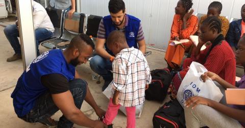 Uno de los niños es vestido con ropa y zapatos nuevos antes partir de Libia
