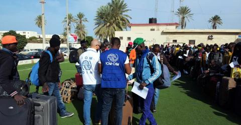 IOM staff with the Burkinabe migrants prior to their departure from Libya.