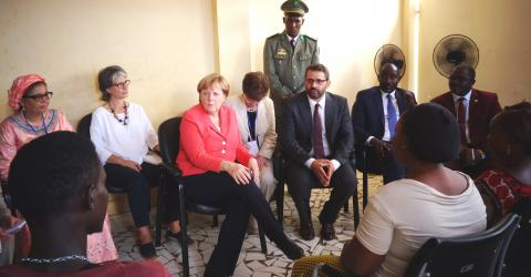 German Chancellor Angela Merkel listens to migrants talk about their stories of migration at IOM's transit centre in Niamey, Niger, on 10 October, 2016.
