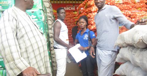 A returnee learns about the vegetable retail business. Photo: IOM