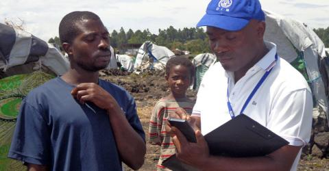 An IOM staffer assesses conditions at Nzula IDP site. Photo:  IOM
