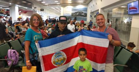 A stranded Cuban family waiting to take a flight out of Costa Rica, displaying the flag of the country that hosted them for almost three months. Photo: Jorge Gallo, IOM.