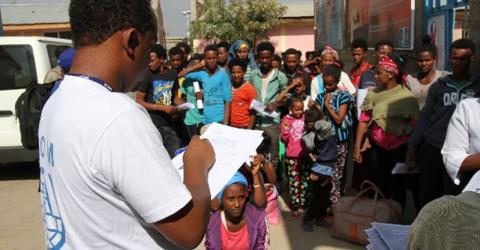 IOM registering refugees before they board a bus for Adi Harush refugee camp, Ethiopia. Photo: IOM