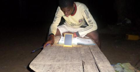 One of the rescued Ghanaian children studies his lessons at night despite power cuts with the aid of a solar lantern he received under IOM's Global Solar Lanterns Initiative. © IOM 2015