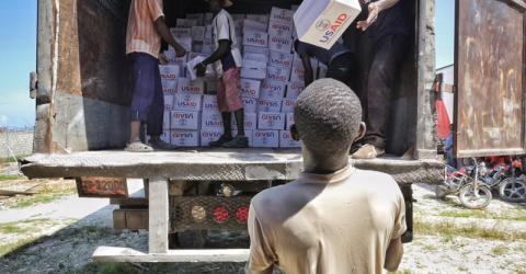 NFIs provided by USAID/OFDA are unloaded from IOM trucks in Jeremie, Haiti. Photo: Hajer Naili / IOM 2016.
