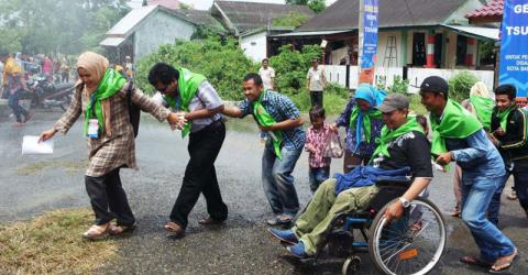 A disabled family is helped to safety in the disaster simulation. Photo: IOM