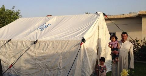 A displaced Iraqi family stand outside their tent near Tikrit. Over 3.3 million people are displaced across Iraq. File photo: IOM 2015