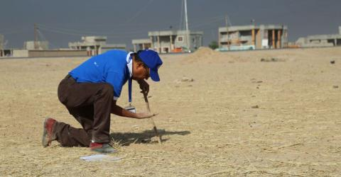 An IOM engineer tests the soil at an emergency camp site at Haji Ali, Ninewa governorate. Photo: IOM