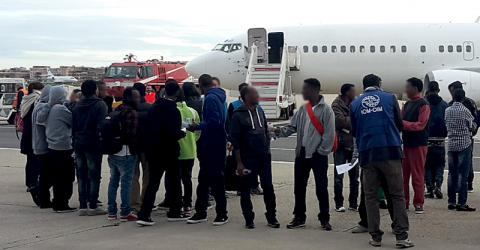 IOM staff with the asylum seekers on their flight to Scandinavia.