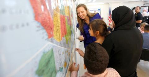 Young Syrian refugees study a map of the US at IOM's Amman office. Photo: Victoria Hazou / IOM