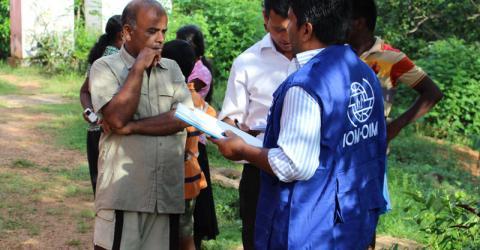 Miembros del personal de la OIM entrevistan a familias desplazadas por las inundaciones en un centro de evacuación en una escuela local. Foto: OIM / Upali Jayasuriya 2016