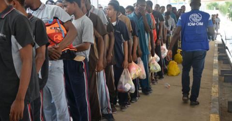 Migrantes de Guinea esperan en fila para abordar el vuelo chárter en el aeropuerto de Mitiga en Trípoli. Foto: OIM 2016